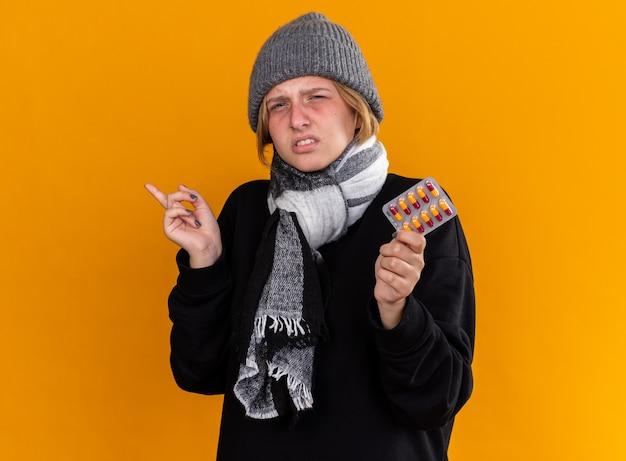 Ungesunde junge frau mit warmem hut und schal um den hals, die sich krank fühlt und an erkältung und grippe leidet, die pillen hält, die mit dem zeigefinger zur seite über der orangefarbenen wand stehen