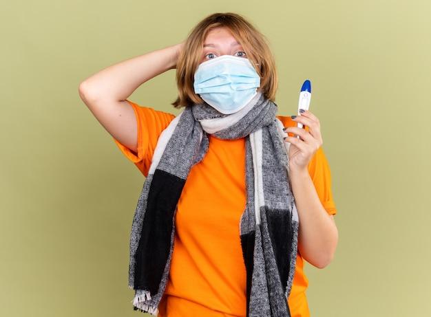 Ungesunde junge frau mit warmem schal um den hals, die eine schützende gesichtsmaske trägt, die an erkältung und grippe leidet und ein fieberthermometer mit fieber hat, das besorgt über der grünen wand steht