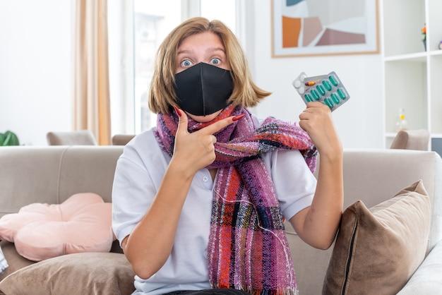 Ungesunde junge frau mit warmem schal um den hals mit gesichtsschutzmaske, die sich unwohl und krank fühlt und an grippe und erkältung leidet, die pillen hält, die verwirrt auf der couch im hellen wohnzimmer sitzen