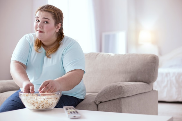Ungesunde nahrung. pralle junge frau, die sich schuldig fühlt, popcorn zu essen, während sie show sieht