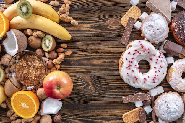 Ungesunde und gesunde süßigkeiten auf hölzernem hintergrund