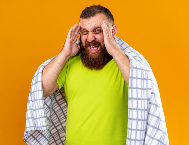 Ungesunder bärtiger mann, der in eine decke gehüllt ist und sich krank fühlt und unter kälte leidet, die die temperatur mit einem thermometer mit starken kopfschmerzen überprüft
