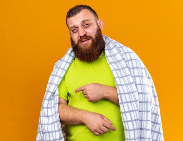Ungesunder bärtiger mann, der in eine decke gehüllt ist und sich krank fühlt und unter kälte leidet, die die temperatur mit einem thermometer überprüft