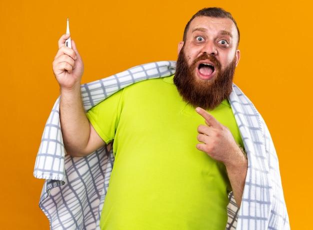 Ungesunder bärtiger mann, der in eine decke gehüllt ist und sich krank fühlt und unter kälte leidet, indem er ein thermometer verwendet, das mit dem finger darauf zeigt, besorgt