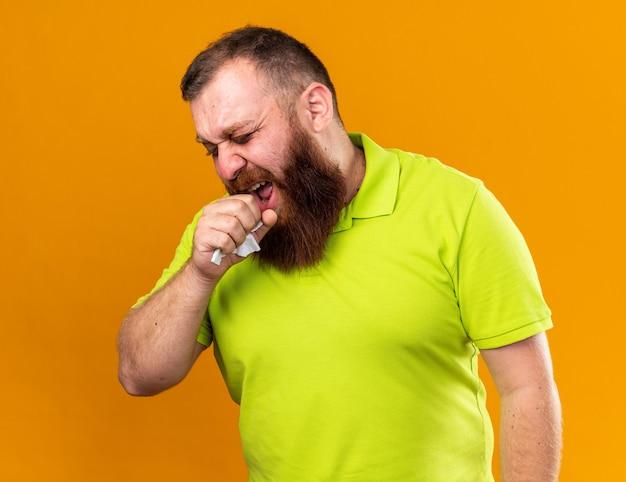 Ungesunder bärtiger mann in gelbem polohemd, der schrecklich an kaltem husten leidet