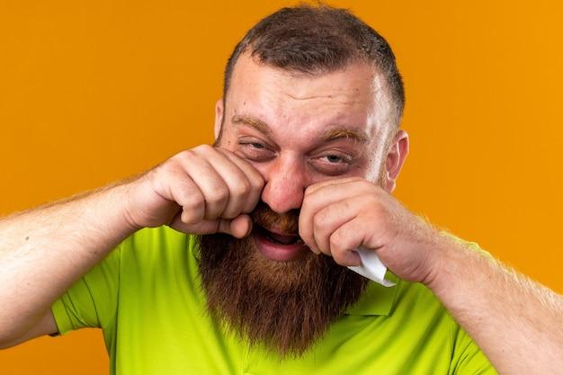Ungesunder bärtiger mann in gelbem polohemd, der schrecklich unter kälte leidet und kopfschmerzen hat, weil die nase über der orangefarbenen wand steht?