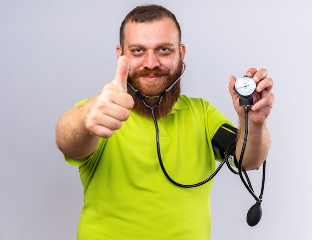 Ungesunder bärtiger mann in gelbem polohemd, der sich besser fühlt, indem er den blutdruck mit einem tonometer misst und lächelt und daumen nach oben über weißer wand zeigt