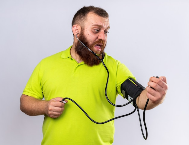 Ungesunder bärtiger mann in gelbem polohemd, der sich krank fühlt, indem er den blutdruck mit einem tonometer misst und besorgt über der weißen wand steht looking