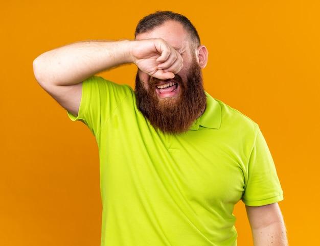 Ungesunder bärtiger mann in gelbem polohemd, der sich schrecklich unter kalten weinenden, harten augen reibt, die über oranger wand stehen?