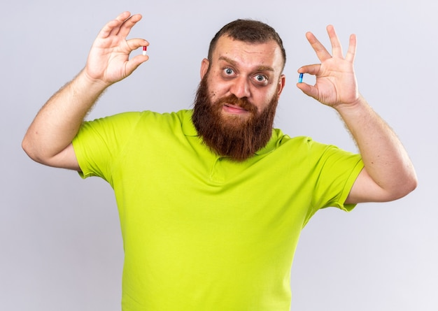 Ungesunder bärtiger mann in gelbem polohemd, der verschiedene pillen hält und sich krank fühlt und an grippe leidet