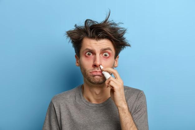 Ungesunder kranker mann mit haarstörung verwendet nasentropfen, behandelt erkältungssymptome, hat juckende augen, leidet im winter an rhnitis, isoliert an der blauen wand, heilt verstopfte nase. medizin-konzept