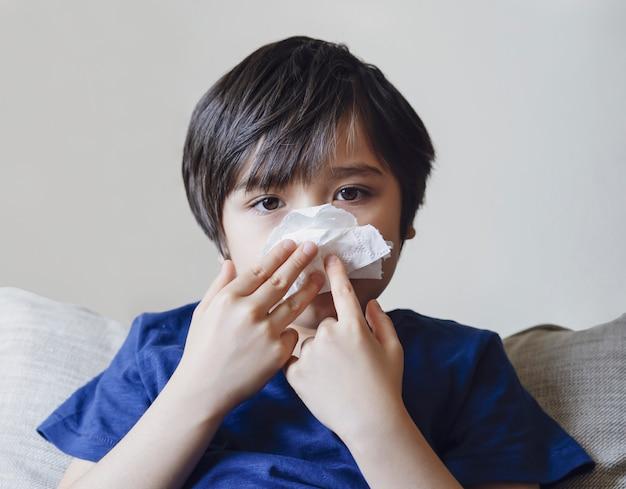 Ungesundes kind putzt nase in gewebe, kind leidet an laufender nase oder niesen, ein junge erkältet sich beim wechsel der jahreszeit, kindheit wischt nase mit gewebe ab
