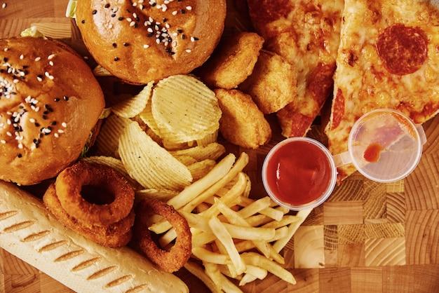 Ungesundes und junk food. verschiedene arten von fast food auf dem tisch, hautnah