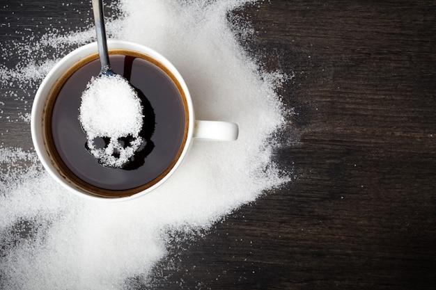 Ungesundes weißzuckerkonzept. schädellöffel mit zucker und tasse schwarzen kaffees auf hölzernem hintergrund