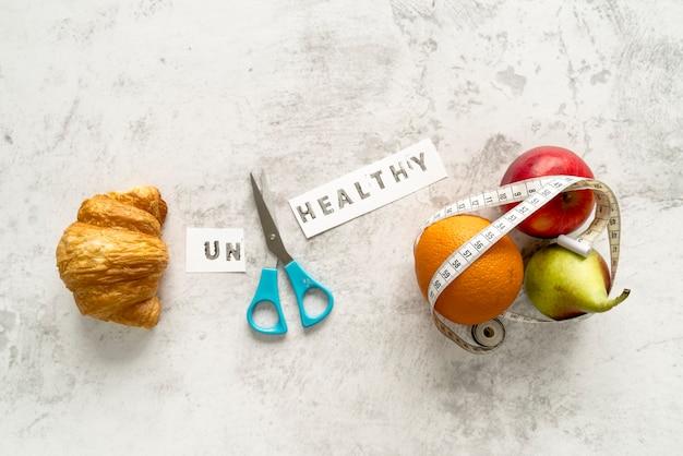 Ungesundes wort und scissor mit dem lebensmittel, das gesundes und ungesundes konzept zeigt