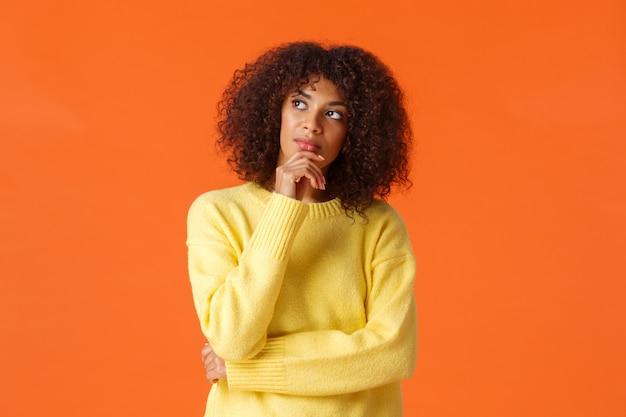 Ungewisser, durchdachter junger kreativer weiblicher unternehmer des afroamerikaners des oberkörperporträts, der neue ideen macht und steht orange und sucht die inspiration und denkt, oben schauend