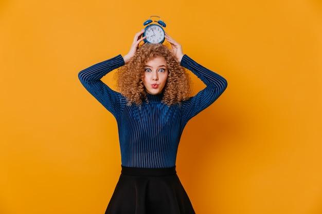 Ungewöhnlich schöne frau in blauem pullover und schwarzem rock schaut in die kamera und hält wecker auf dem kopf.