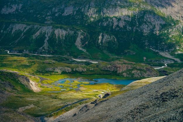 Ungewöhnlich schöner see im hochlandtal und im fluss entlang des hohen berges. malerische alpine landschaft mit kleinem blauen bergsee und wasserläufen zwischen moosen und felsen. fantastische grüne luftlandschaft.