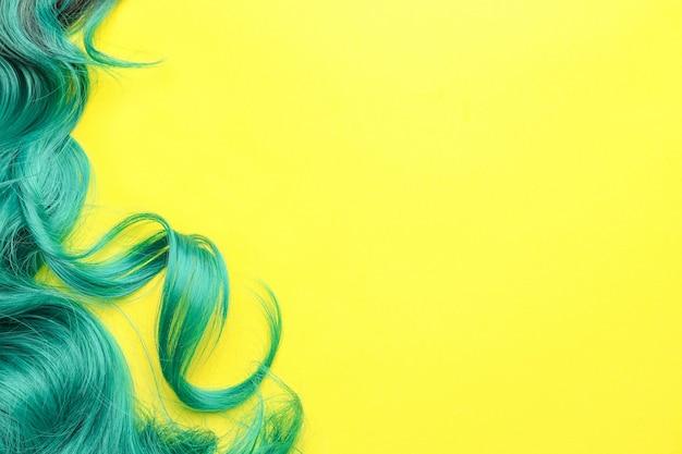 Ungewöhnliche grüne perücke auf gelbem hintergrund