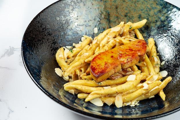Ungewöhnliche hausgemachte italienische pasta mit foie gras leber in einer stilvollen schwarzen schüssel auf einem marmor