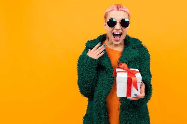 Ungewöhnliche hübsche frau mit dem kurzen rosa haar und tätowierung schreit mit glück und hält einen weißen kasten mit dem geschenk, das auf orange lokalisiert wird