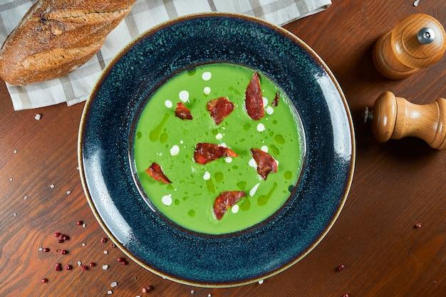 Ungewöhnliche und feinschmeckerische grüne sahnesuppe mit chorizo-wurst und olivenöl, sahne in einer blauen schüssel auf einem holztisch. restaurant essen. abendessen. draufsicht essen
