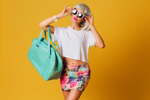 Ungewöhnliches hübsches blondes mädchen des modestudio-porträts in der kurzen partyperücke, im weißen oberteil und im sexy rock, die innen auf gelbem hintergrund aufwerfen. sonnige positive emotionen, stilvolle sonnenbrille.