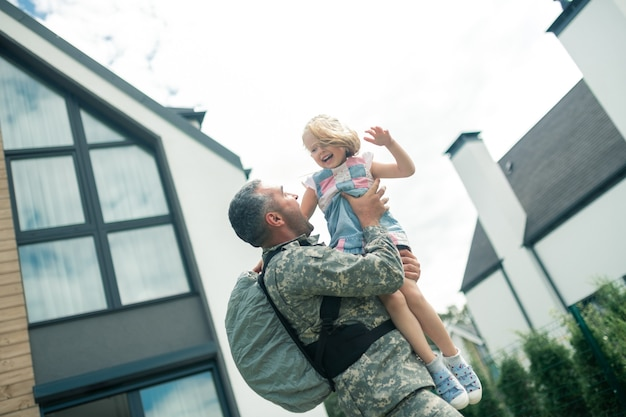 Unglaublich fühlen. militäroffizier mit rucksack und unglaublichem anblick seiner tochter