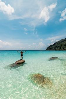 Unglaubliche aufnahme eines mannes, der sich bereit macht, an einem ruhigen, friedlichen strand zu schwimmen?