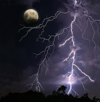 Unglaubliche blitzeinschläge in den nachthimmel mit gruseligem vollmond