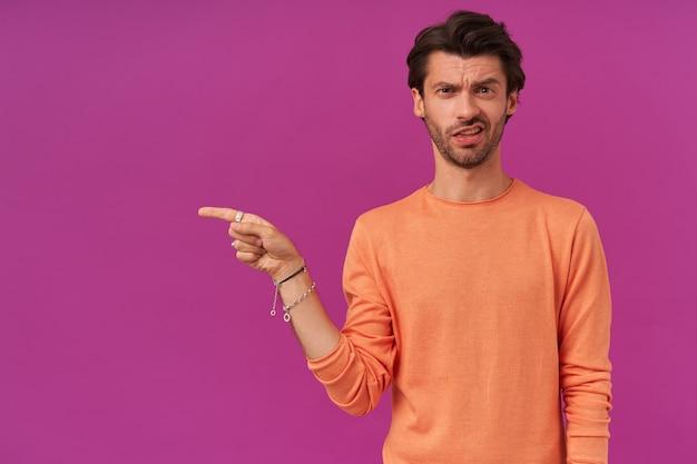 Unglaublicher kerl mit brünetten haaren und borsten, der finger nach links am kopierplatz zeigt
