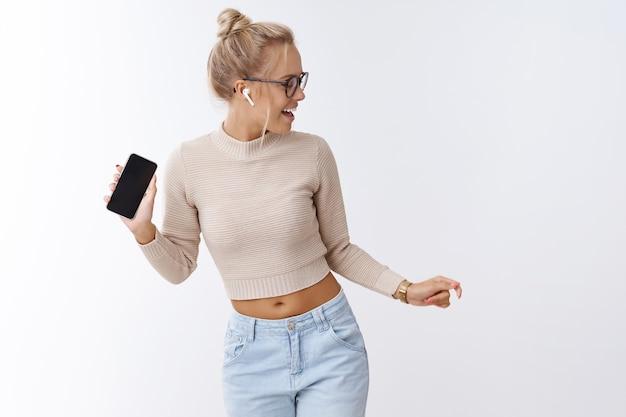 Unglaublicher klang. innenaufnahme einer amüsierten und enthusiastischen charismatischen blonden eleganten frau, die in drahtlosen kopfhörern tanzt, die smartphone-musik hört und das mitsingen genießt