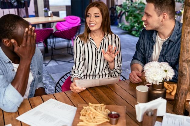 Unglaublicher klatsch von der frau zu den besten freunden beim informellen jahrestreffen im gemütlichen restaurant