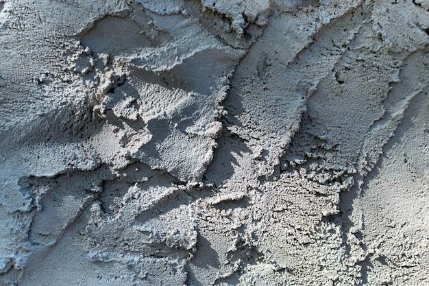 Ungleichmäßiger betonwandhintergrund, graue putzstruktur, körniger zement mit strukturierten schichten und schatten.