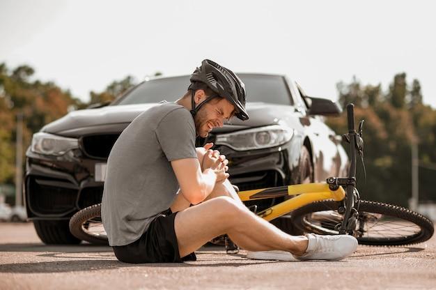 Unglück. unglücklicher kerl im helm, der mit geschlossenen augen sitzt und sein knie in der nähe des fahrrads auf der straße vor dem auto hält