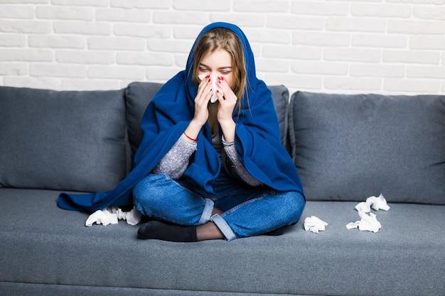 Unglücklich verärgert sitzt müde frau auf einem sofa zu hause, leidet an einer erkältung und benutzt servietten, wird kalt