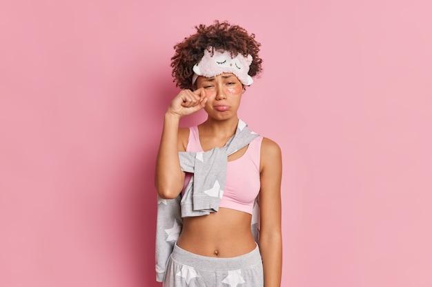 Unglückliche afroamerikanerin reibt sich die augen hat einen schläfrigen ausdruck, wischt tränen ab und trägt kollagenflecken unter den augen auf