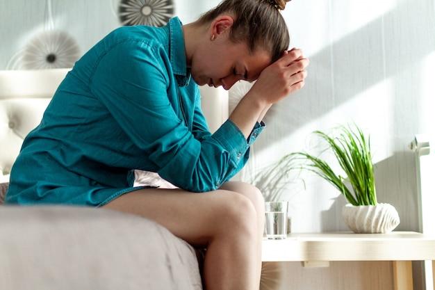 Unglückliche, alleinstehende, depressive frau, die sich einsam, wehrlos und müde fühlt. unter kopfschmerzen, migräne und schmerzen leiden