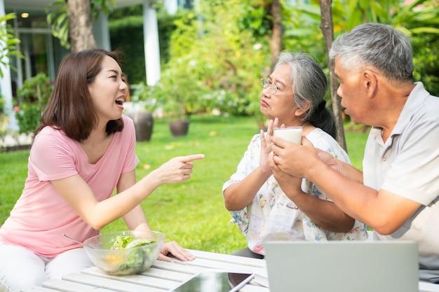 Unglückliche anorexie der asiatischen seniorin und nein zu den mahlzeiten, ältere leben mit familie und pflegekräften versuchen futtermittel und alte frau keinen appetit, konzept des gesundheitswesens und älterer pflegekräfte