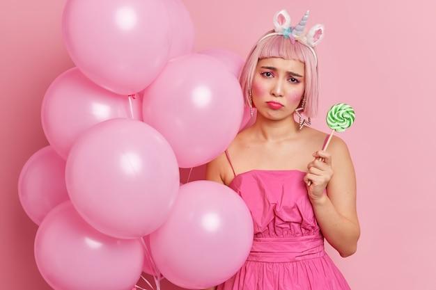 Unglückliche asiatin mit rosiger bob-frisur trägt festliches kleid, hält lutscher und luftballons, die mit etwas verärgert sind