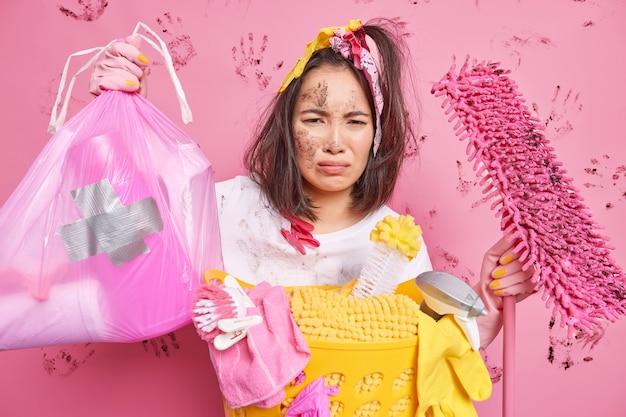 Unglückliche asiatin mit schmutzigem gesicht hat müden, unzufriedenen ausdruck, sammelt müll zu hause und hält mop damit beschäftigt, waschposen in der nähe des wäschekorbs einzeln über rosafarbener wand zu machen