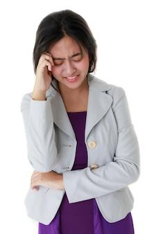 Unglückliche asiatische frau, die unter kopfschmerzen leidet und den kopf auf weißem hintergrund im studio berührt.