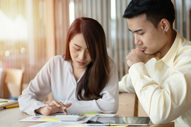 Unglückliche asiatische paare berechnen einnahmen und ausgaben, um unnötige ausgaben zu senken.