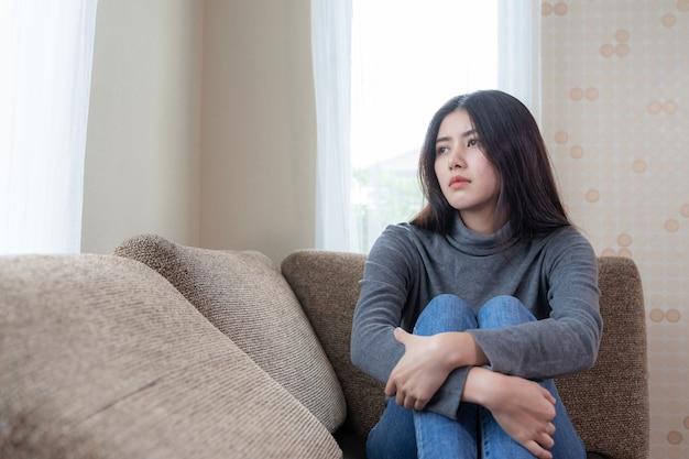 Unglückliche asiatische recht junge frau, die allein auf couch mit glaubender traurigkeit stationiert