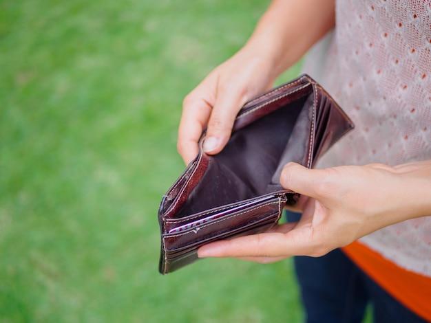 Unglückliche bankrotte frau mit leerer geldbörse. junge frau zeigt ihre leere geldbörse. konkurs