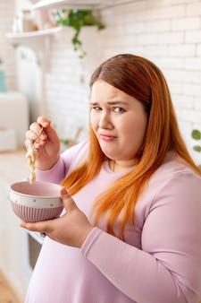 Unglückliche, dicke frau, die ihr essen nicht mag, während sie eine strenge diät einhält