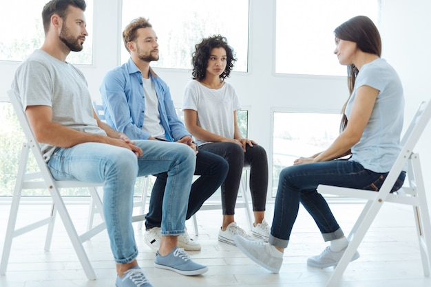 Unglückliche düstere junge leute, die ihrer freundin gegenüber sitzen und ihre geschichte hören, während sie eine gruppentherapiesitzung haben
