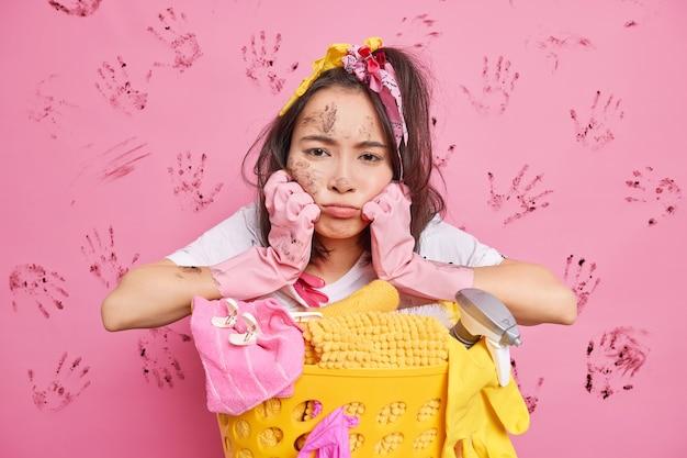 Unglückliche erschöpfte frau, die müde ist vom waschen und hausarbeit, lehnt sich an den wäschekorb mit reinigungsmitteln posen unordentlich trägt gummischutzhandschuhe posen gegen rosa wand