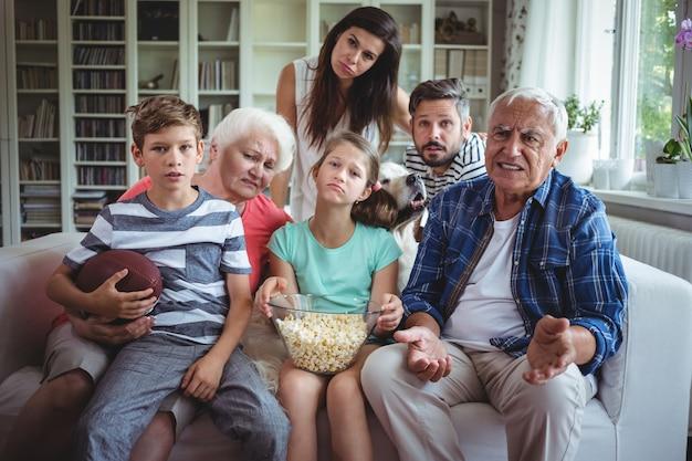 Unglückliche familie, die fußballspiel im fernsehen im wohnzimmer sieht