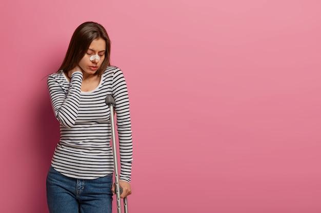 Unglückliche frau berührt den nacken vor schmerzen, leidet nach einem schrecklichen vorfall